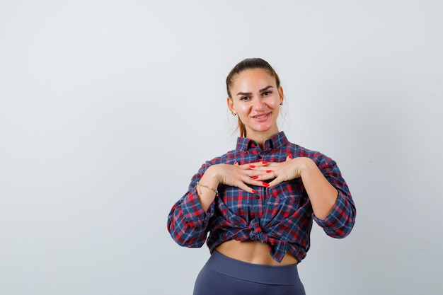 Jonge vrouw met handen op de borst in geruit hemd, broek en vrolijk, vooraanzicht.