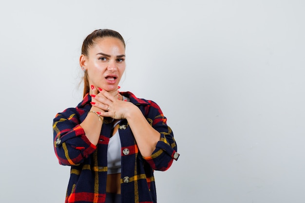 Jonge vrouw met handen op de keel in crop top, geruit hemd en onwel, vooraanzicht.