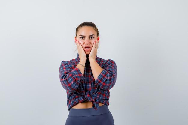 Jonge vrouw met handen op de wangen in geruit hemd, broek en verbaasd, vooraanzicht.