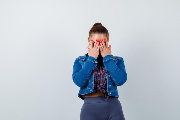 Jonge vrouw met handen op gezicht in geruit overhemd, jas, broek en weemoedig kijken. vooraanzicht.