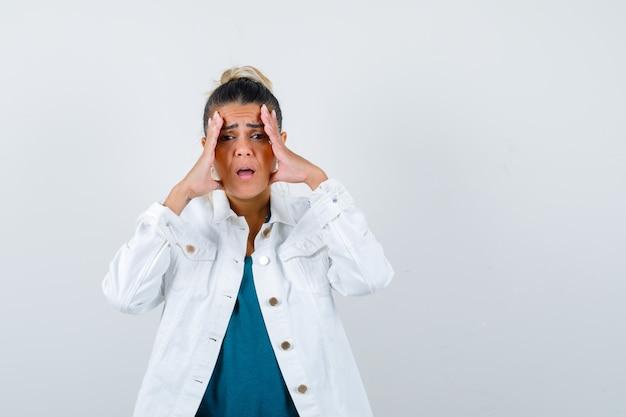 Jonge vrouw met handen op gezicht in wit jean-jasje en op zoek boos, vooraanzicht.