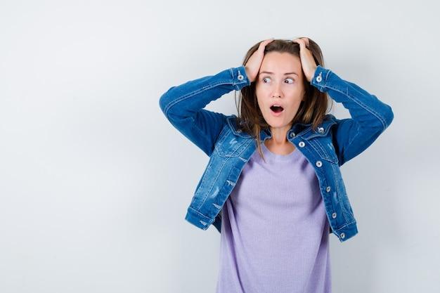 Jonge vrouw met handen op het hoofd, opzij kijkend in t-shirt, jas en geschokt. vooraanzicht.