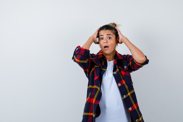 Jonge vrouw met handen op het hoofd, shirt en verbaasd kijken, vooraanzicht.