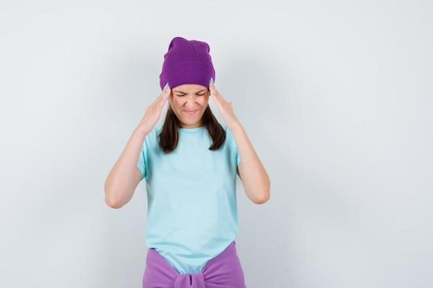 Jonge vrouw met handen op slapen, grimassen in blauw t-shirt, paarse muts en gehaast kijken, vooraanzicht.