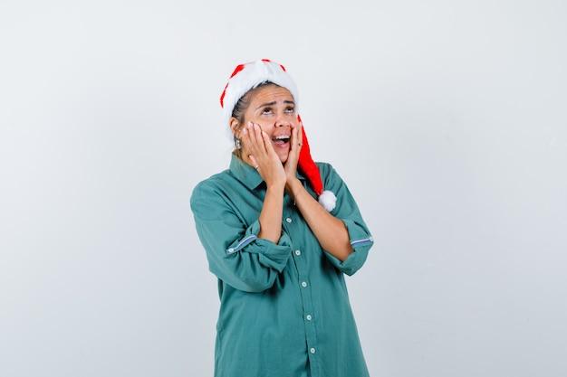 Jonge vrouw met handen op wangen, mond openend in shirt, kerstmuts en geschokt kijken. vooraanzicht.