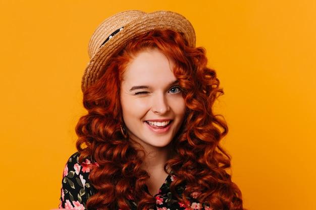 Jonge vrouw met helder krullend haar en blauwe ogen in goed humeur knipoogt, poseren in hoed op oranje ruimte.