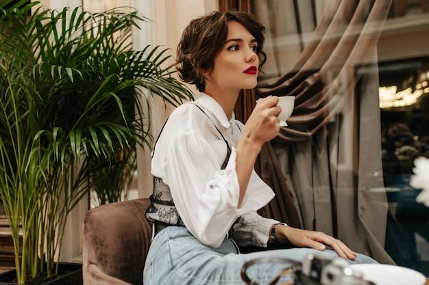 Jonge vrouw met heldere lippen en krullend haar vormt in restaurant. trendy vrouw in wit overhemd en spijkerbroek houdt kopje koffie in café.