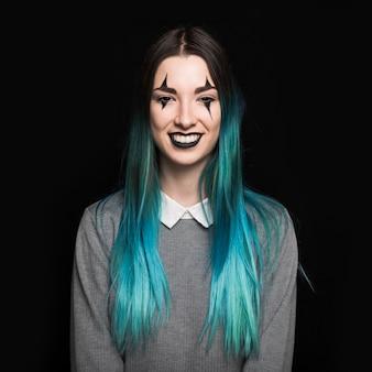Jonge vrouw met het blauwe haar stellen in studio