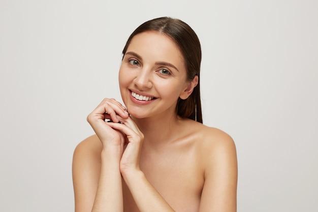 Jonge vrouw met het perfecte gezonde frisse huid glimlachen