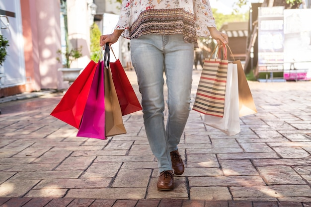 Jonge vrouw met het winkelen zakken bij winkelcomplex op zwarte vrijdag, het concept van de vrouwenlevensstijl