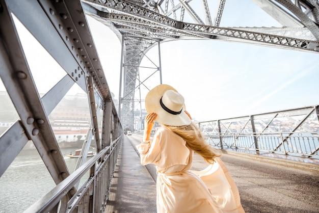 Jonge vrouw met hoed die geniet van een prachtig uitzicht op de beroemde ijzeren brug tijdens het mistige en winderige weer in porto, portugal