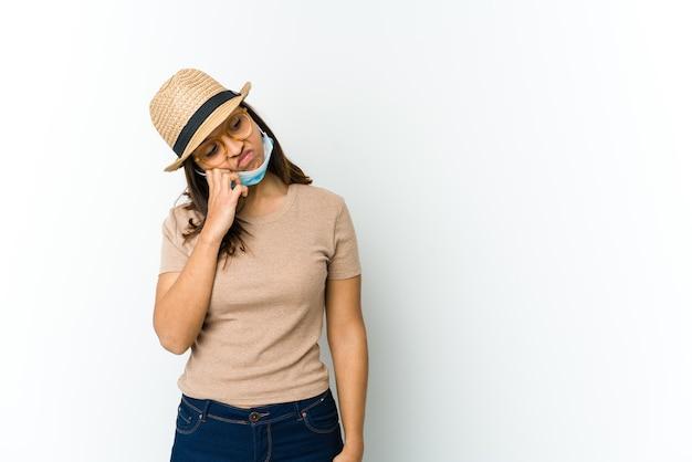 Jonge vrouw met hoed en masker om te beschermen tegen covid geïsoleerd op een witte muur die zich verdrietig en peinzend voelt, kijkend naar kopie ruimte