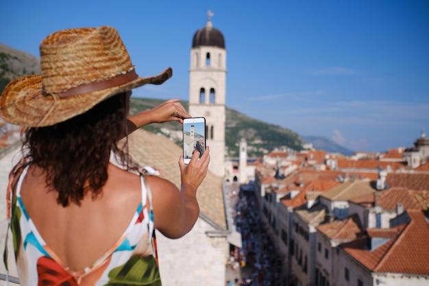 Jonge vrouw met hoed neemt foto met mobiel in dubrovnik, kroatië