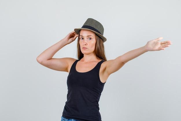 Jonge vrouw met hoed terwijl het strekken van arm in hemd, korte broek vooraanzicht.