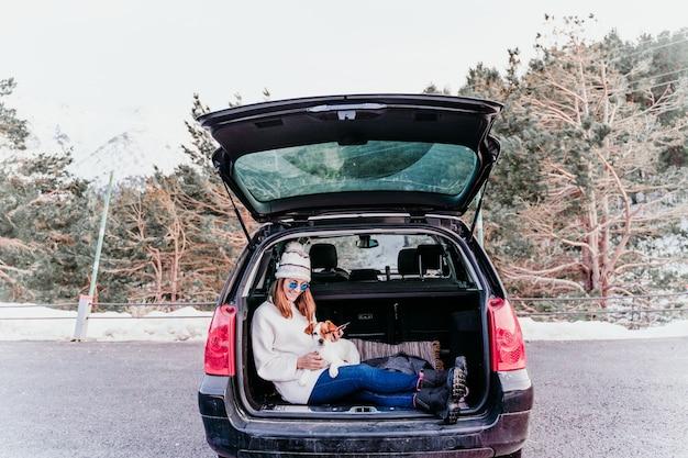 Jonge vrouw met hond in auto die pret heeft. besneeuwde berg.