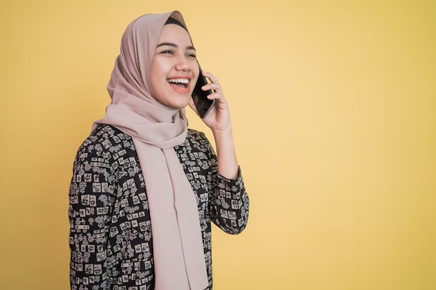 Jonge vrouw met hoofddoek die breed glimlacht terwijl ze wordt gebeld met een blij gebaar met copyspace