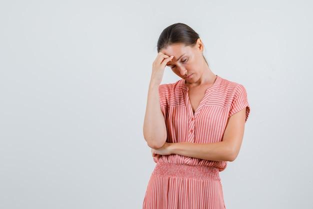 Jonge vrouw met hoofdpijn in gestreepte jurk en op zoek moe. vooraanzicht.