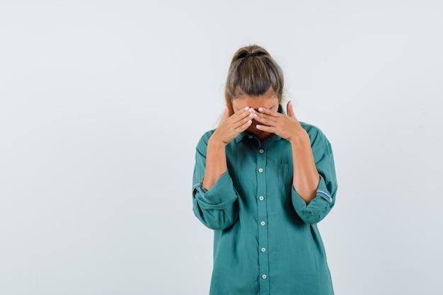 Jonge vrouw met hoofdpijn in groene blouse en moe op zoek