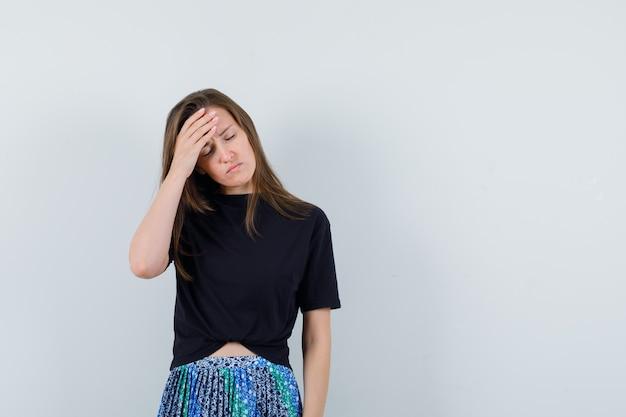 Jonge vrouw met hoofdpijn in zwart t-shirt en blauwe rok en ziet er moe uit