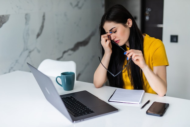 Jonge vrouw met hoofdpijn tijdens het werken op laptop