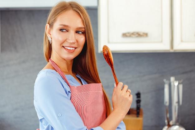 Jonge vrouw met houten lepel in de keuken