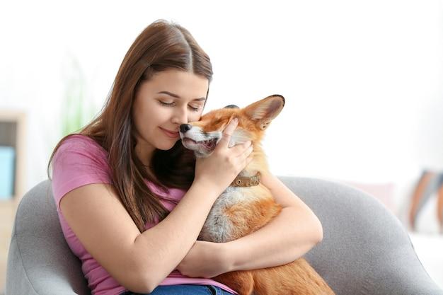 Jonge vrouw met huisdier vos binnenshuis