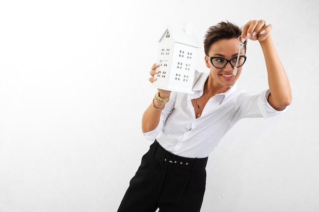 Jonge vrouw met huismodel en sleutels op wit