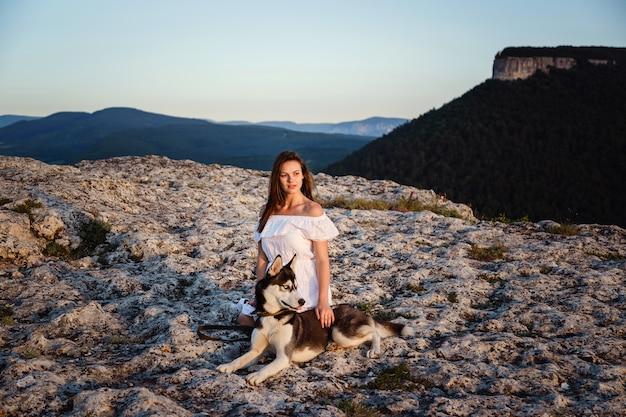 Jonge vrouw met husky hond op een zonnige dag zitten in het hooggebergte