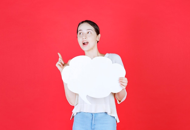 Jonge vrouw met ideeënbord en wijsvinger omhoog