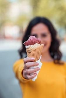 Jonge vrouw met ijsje naar camera, focus op de voorgrond.