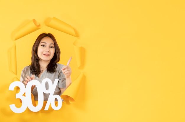 Jonge vrouw met inscriptie teken op gescheurde gele papier achtergrond geld verkoop