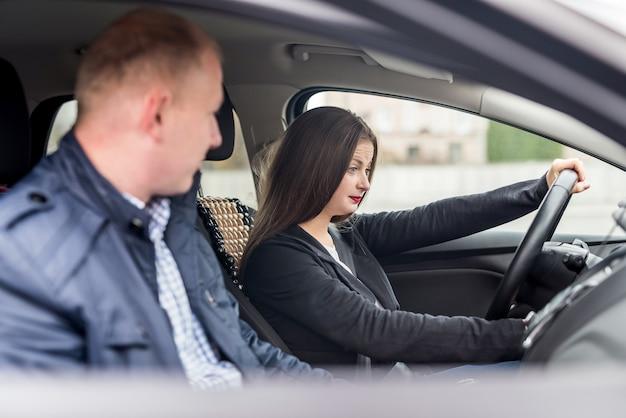 Jonge vrouw met instructeur die in de auto zit