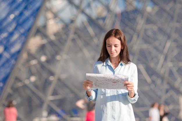 Jonge vrouw met kaart in europese stad in openlucht