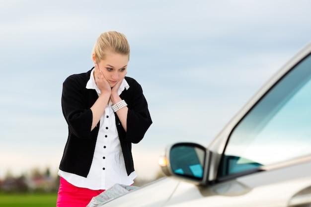 Jonge vrouw met kaart op auto die wordt verloren