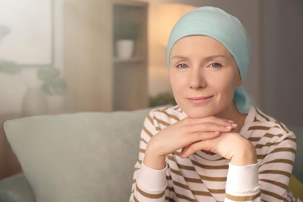 Jonge vrouw met kanker in hoofddoek binnenshuis