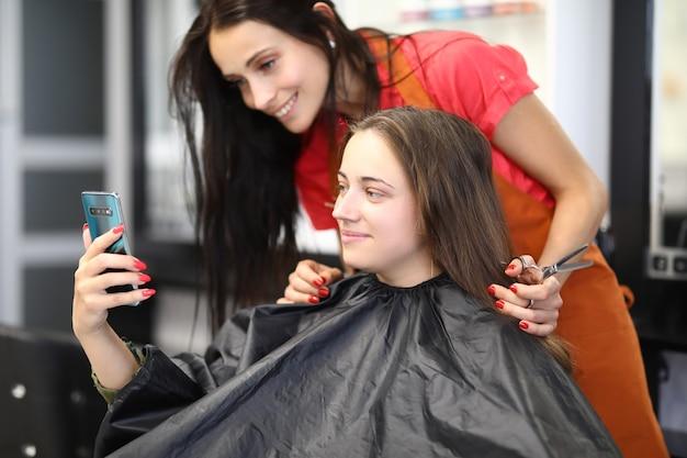 Jonge vrouw met kapper zit in schoonheidssalon en selfie te nemen op smartphone
