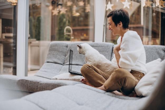 Jonge vrouw met kat die op laptop van huis werkt