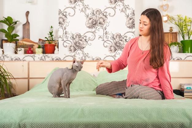 Jonge vrouw met katten die pret in de slaapkamer hebben. blijf thuis concept.
