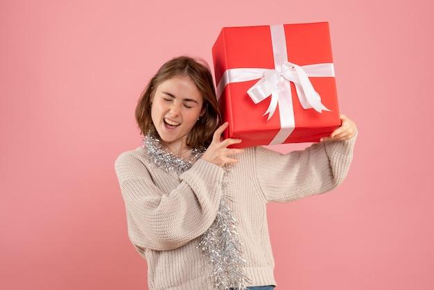 Jonge vrouw met kerst aanwezig gevoel opgewonden op roze