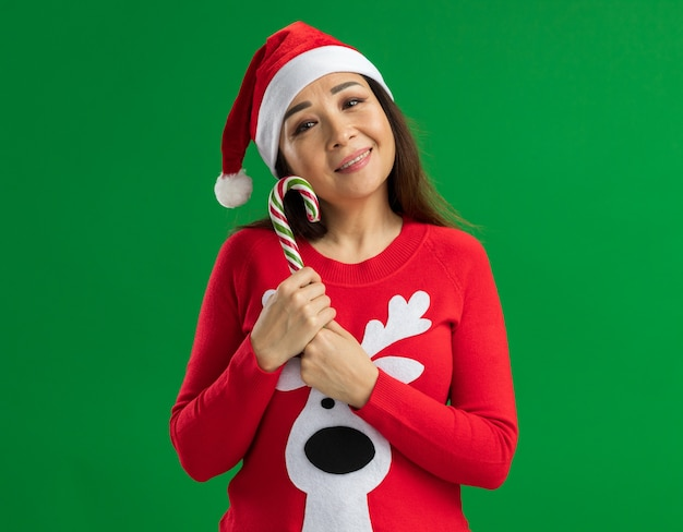 Jonge vrouw met kerst kerstmuts en rode trui bedrijf candy cane camera kijken met glimlach op gezicht staande over groene achtergrond