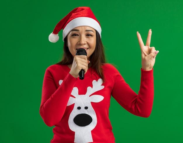 Jonge vrouw met kerst kerstmuts en rode trui praten met microfoon glimlachend vrolijk tonen v-teken staande over groene achtergrond