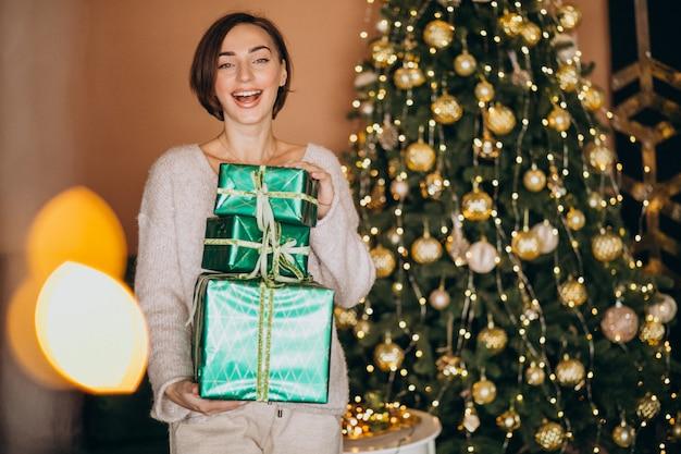 Jonge vrouw met kerstcadeau bij de kerstboom