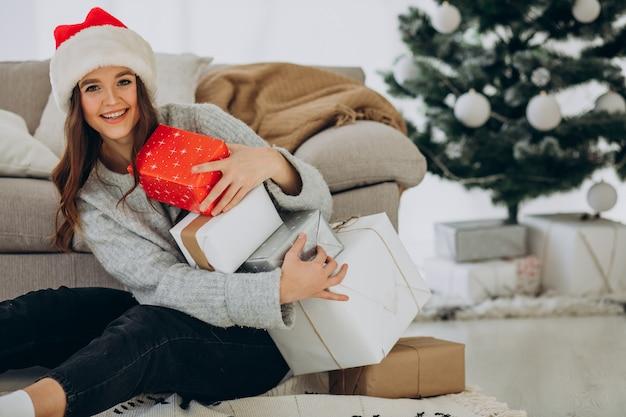 Jonge vrouw met kerstcadeautjes bij de kerstboom
