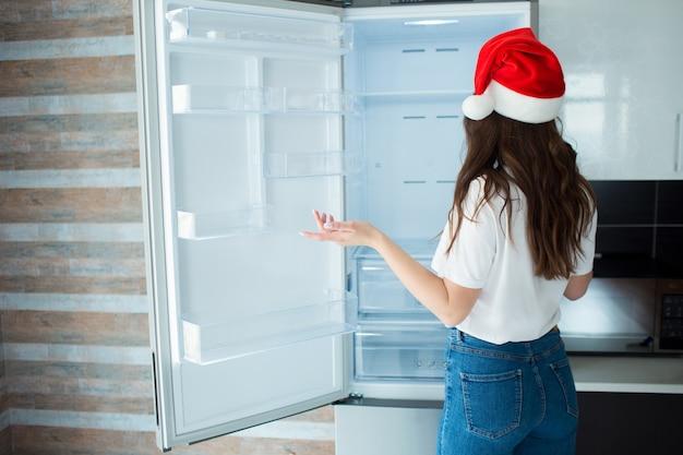 Jonge vrouw met kerstmanhoed die zich voor lege koelkast bevindt