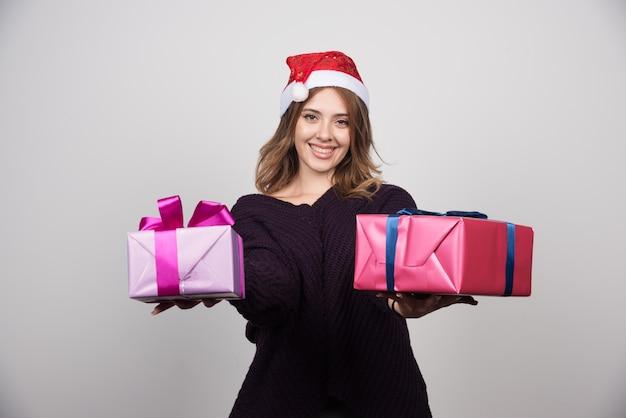 Jonge vrouw met kerstmuts die geschenkdozen aanbiedt.
