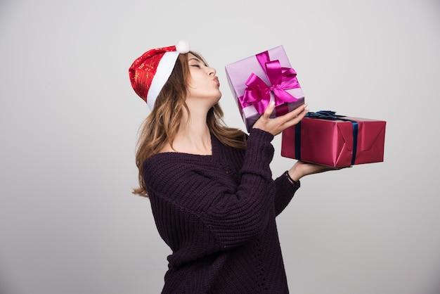 Jonge vrouw met kerstmuts met geschenkdozen presenteert.