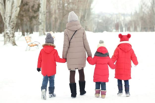 Jonge vrouw met kinderen die op sneeuw lopen