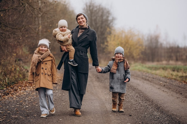 Jonge vrouw met kinderen wandelen in herfst park