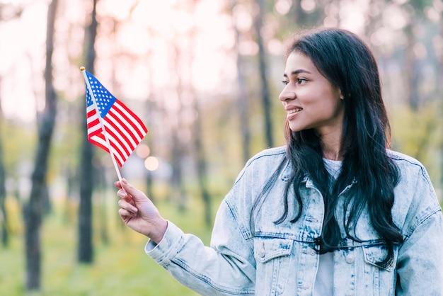 Jonge vrouw met kleine amerikaanse vlag buitenshuis