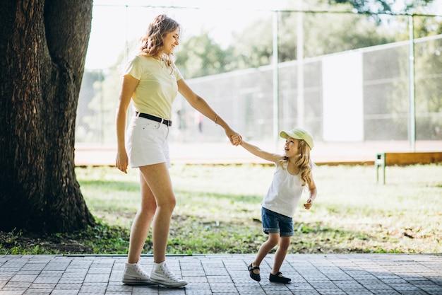 Jonge vrouw met kleine dochter die in park loopt